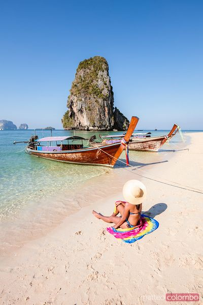 Tourist at the beach near longtail boats, Railay, Thailand