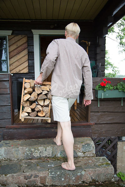 Mies kantamassa puita|||Man carrying a wood for sauna