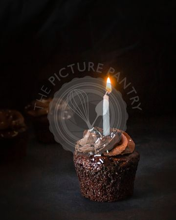 Chocolate cupcake with lit candle.