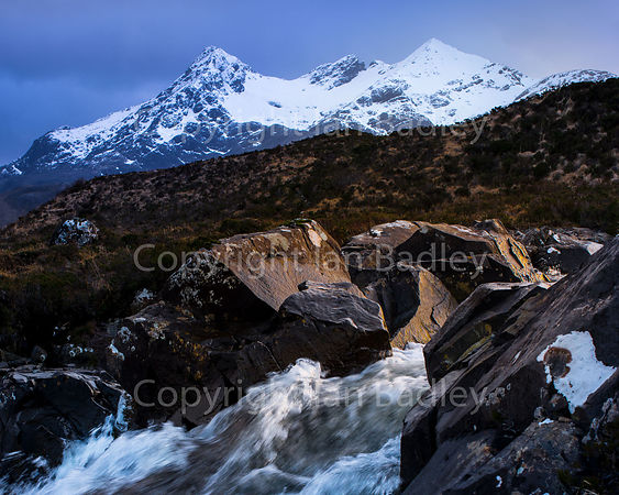 A gushing stream runs over rocks withsnow covered Cuillin Mountains.