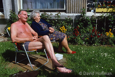 Retired couple relax in the sun outside their council flat on the Chalk Hill Estate, Brent.