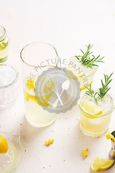 2 glasses and a jug of lemonade garnished with lemon zest and slices and rosemary branches, placed on a white background with...