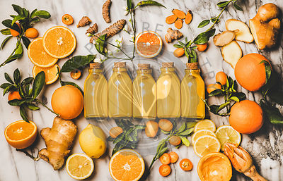 Turmeric, ginger, citrus juice shot in bottles over marble background