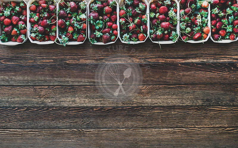 Fresh strawberries in plastic-free containers over wooden background, copy space