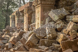A group of stones fallen from the walls of Ta Phrom temple within the Angkor temole comples in Cambodia.