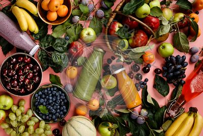 Flat-lay of organic fruits and berries and Freshly blended fruit smoothie on pink background