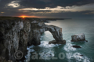 Sunrise with dramatic sky over Green Bridge of Wales, Pembrokeshire,South Wales, UK.