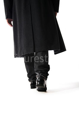 A Figurestock image of a mystery man walking away, in a long black winter coat – shot from low level.