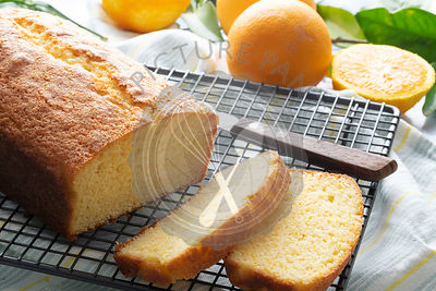Orange cake cooling on cake rack.