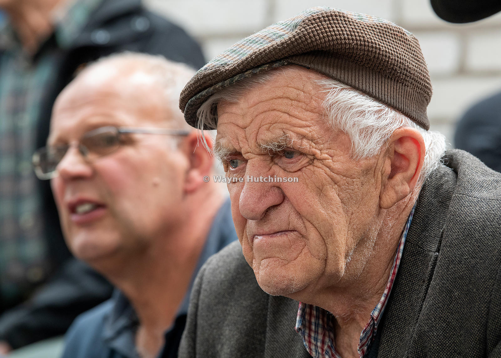Old farmer watching trade at a livestock auction market, Lancashire, UK.
