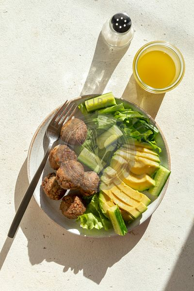 Vegetarian meatballs with lettuce,cucumber and avocado salad in a bowl
