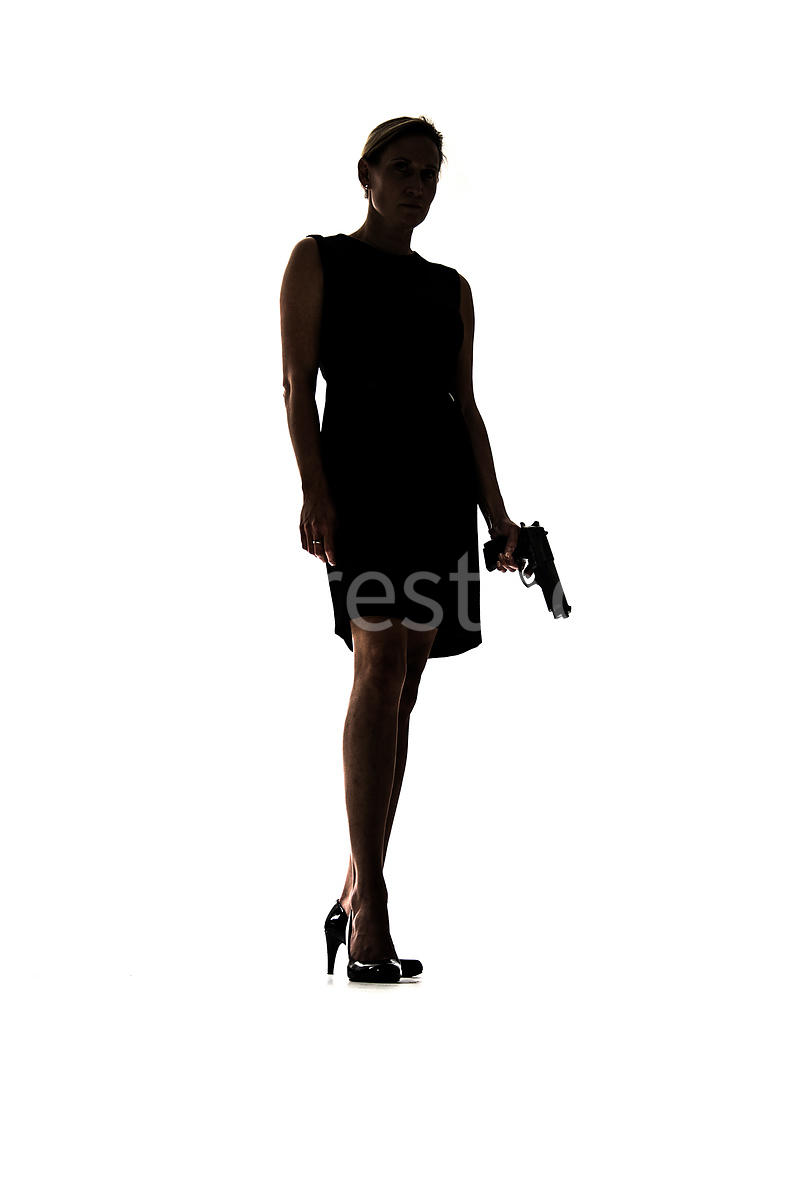 Silhouette of a woman standing with a gun – shot from low level.