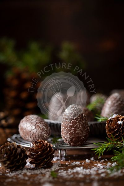 Festive pine cone shaped chocolates on a wire rack surrounded by fir sprigs and real pine cones