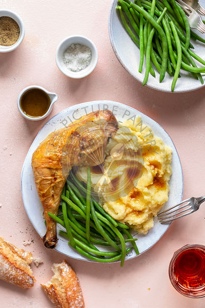 Roasted chicken with mashed potatoes and green beans on a plate