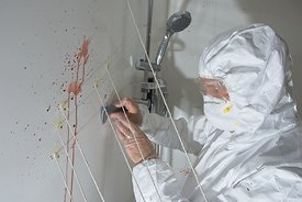 Student measuring blood spatter in University of Derby's Forensic Training Facility. Stringing in place for mesuring angles o...