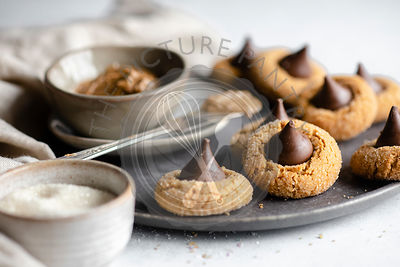 Peanut butter in a pinch bowl on a dark grey plate surrounded by chocolate kisses cookies