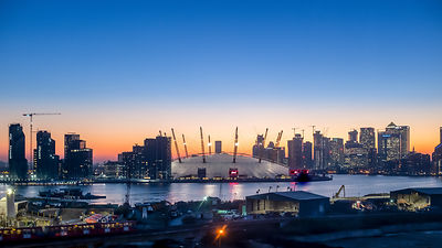 The O2 Arena and surrounding skyline across the River Thames against a golden sunset