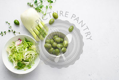 Flatlay with healthy salad ingredients in green color on concrete background.