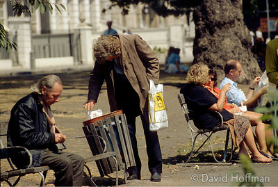Homeless alcoholics mingle with office workers at lunch time in Lincoln's Inn Fields, UK.