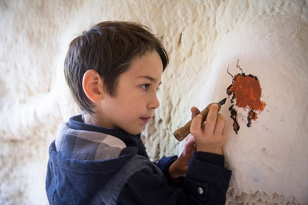 Enfant de 7 ans participant à l'atelier Art Pariétal, Parc du Thot, France / 7-year-old child participating in the Cave Art w...