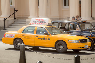 New York City yellow taxi next to a London black cab in London