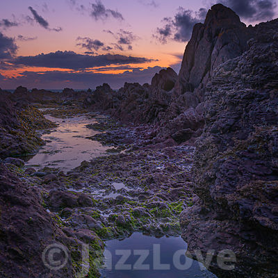 Sunset afterglow on magical rocky beach.