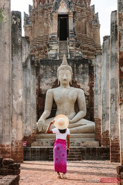 Woman in front of Buddha statue, Si Satchanalai Historical Park, Thailand