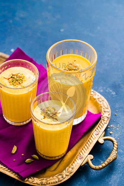 Three glasses of Mango Lassi garnished with saffron and crushed pistachio