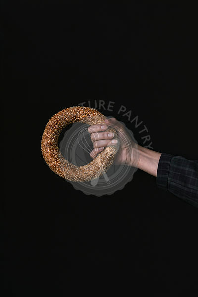 A Hand with a Bagel on a Black Background