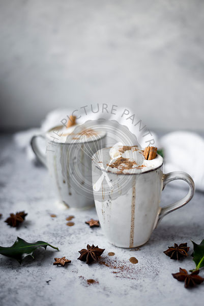 Pumpkin Spiced Latte With Whipped Cream Topping And Cinnamon Dusting Surrounded By Leaves And Spices