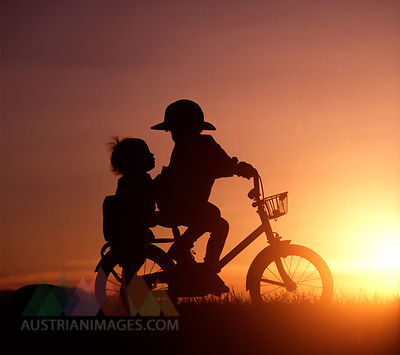Silhouette of two children riding bicycle in sunset