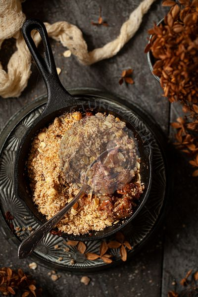 A cast iron skillet holding a part eaten pear and chocolate crumble