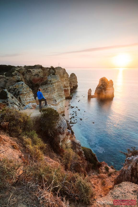 Man standing on a cliff on the coast of Algarve, Portugal