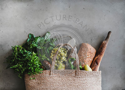 Flat-lay of eco-friendly bag with fresh foods, copy space