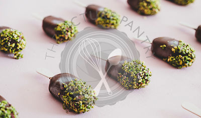 Chocolate glazed ice-cream pops with pistachio icing, close-up