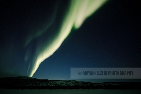Northern lights above fells on the shore of the Teno River