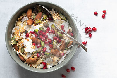 Bowl of muesli topped with almonds, pistachio nuts, dried coconut and pomegranate seeds.