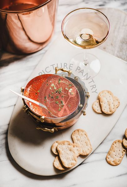 Red caviar with salty crackers and glass of champaigne