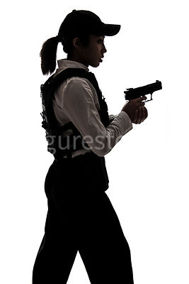 A tough woman FBI agent, in silhouette, holding a gun – shot from mid level.