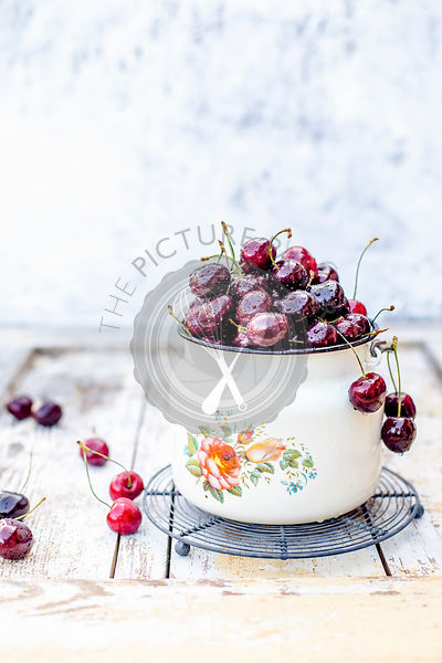 Fresh cherries in enamel bucket