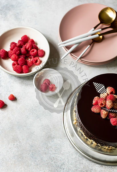 Chocolate truffle cake with raspberries and chocolate decoration on top on the plate