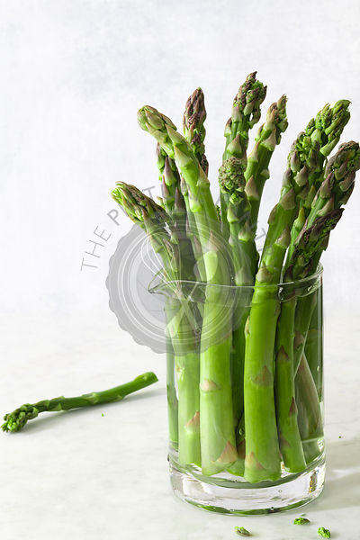 Freshly cut asparagus spears in a glass jug filled with water.