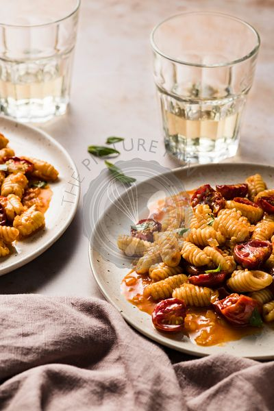 Plates of cavatelli pasta with burst cherry tomatoes and glasses of wine.