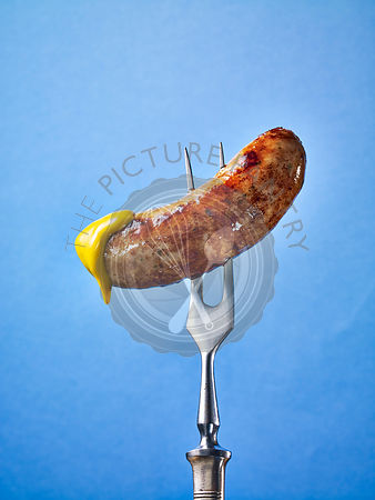 A sausage dipped in mustard on a fork