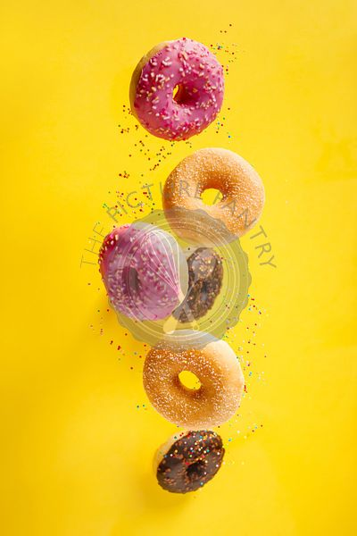 Various decorated doughnuts with sprinkles in motion falling on yelloy background