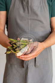 Man holding a bundle of green asparagus in his hands