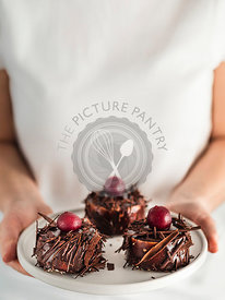 Woman holds three mini black forest cakes