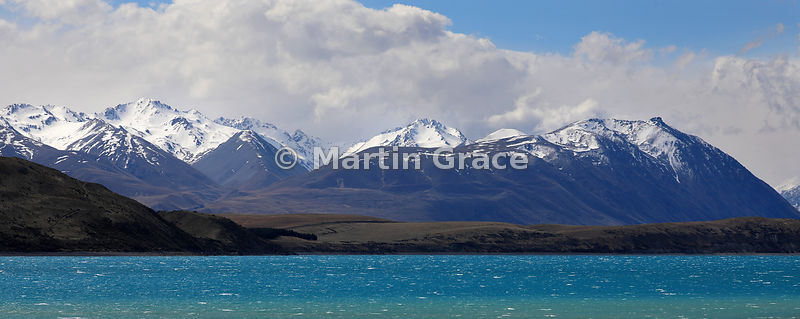 Looking North over the impossibly-aquamarine glacial meltwaters of Lake Tekapo to a backdrop of Southern Alps, Canterbury, So...