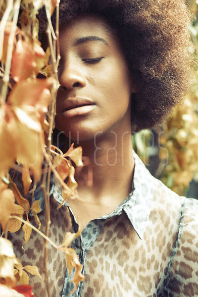 Beautiful Young Black Woman With Curly Hair And Smooth Skin Leaning Against Wall Of Ivy With Her Eyes Closed