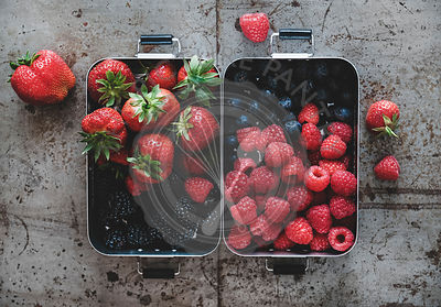 Flat-lay of fresh berries in lunchboxes over rough grey background